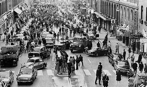 En svartvit bild på en gata med massa bilar och människor.