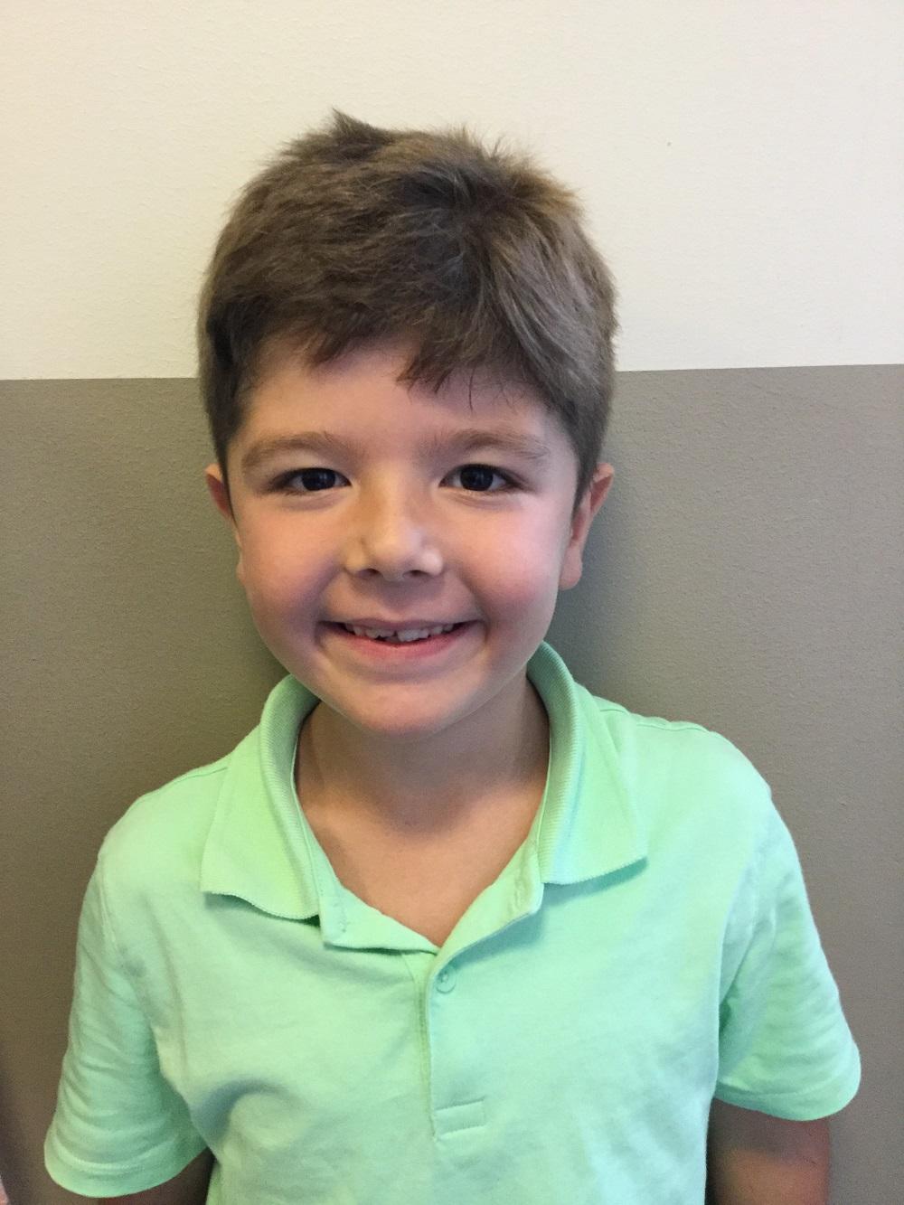Ayham ler stort. Han har brunt rufsigt hår och en grön tröja med krage.