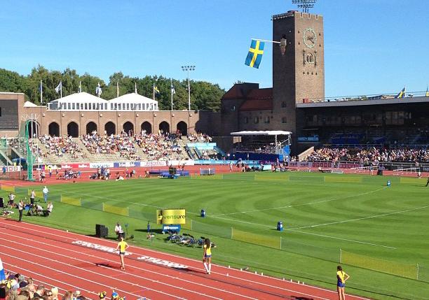 En stadio syns i solsken. På löparbanorna står några svenska idrottare.