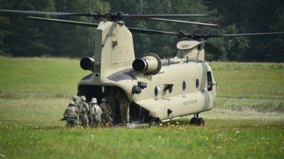 En grön stor helikopter står på en gräsmatta. Flera soldater håller på att gå in i helikoptern.