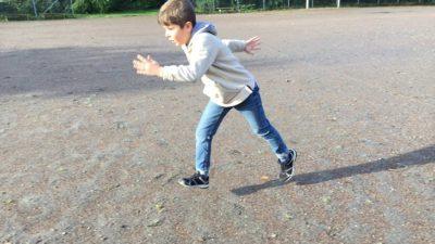 Ayham har blå byxor och ljus jacka. Han är mitt i ett steg och springer över en grusplan.