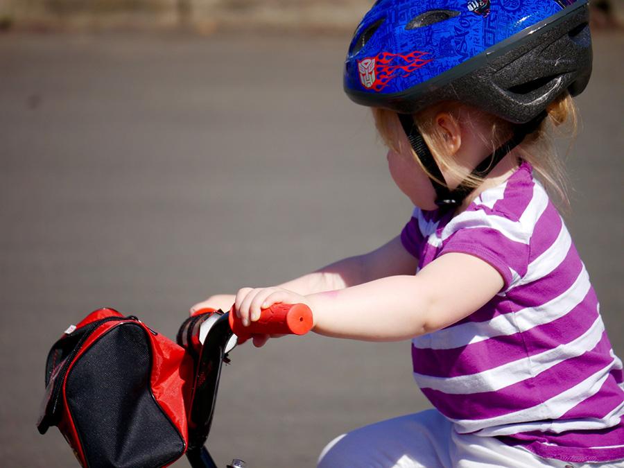 Ett litet barn, kanske 3-4 år, som sitter på en liten cykel. Barnet har hjälm och randig tröja.