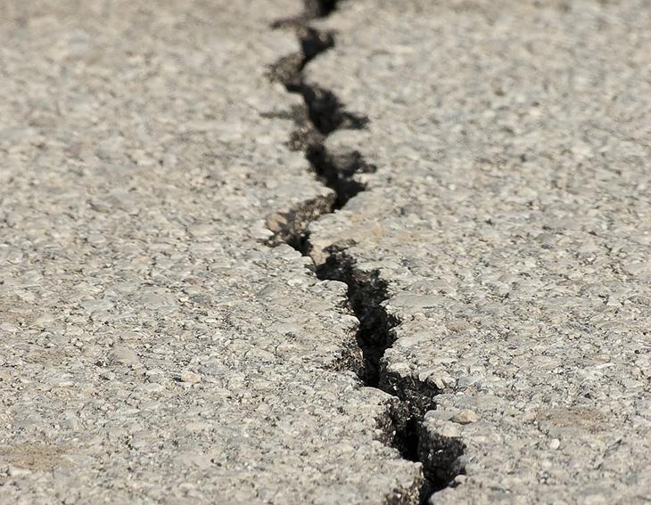 En spricka som går genom asfalt på marken.