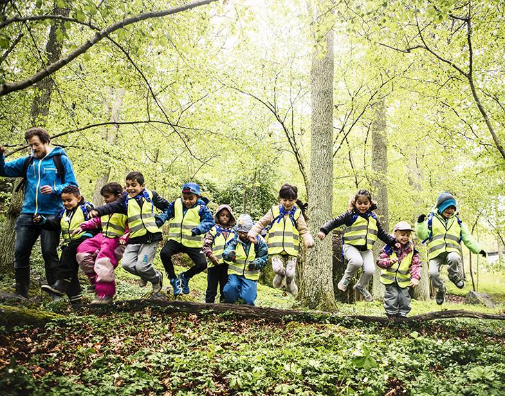 En grupp med barn hoppar över stam i skogen. Alla har reflexväst och ser väldigt glada ut.