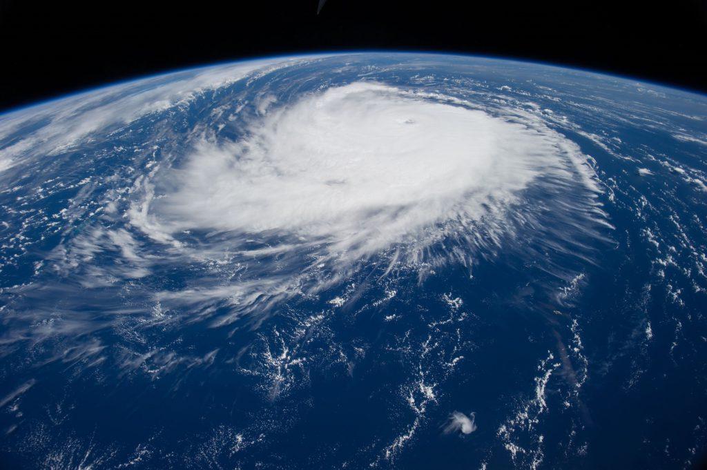En orkan ovanifrån. Det är ett stort vitt, runt moln som ser ut att snurra. Under syns vatten.