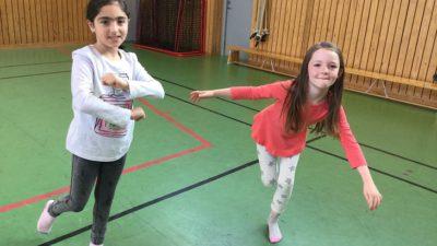 Judith och Kavi står i en gymnastiksal och dansar. En av dem snurrar armarna framför sig och den andra står på ett ben med armana utåt.