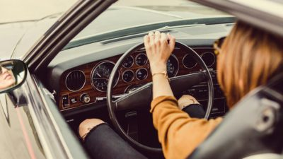 Ett förarsäte snett bakifrån. Ratten syns tydligt, och någon som håller i ratten. personen har långt hår och trasiga jeans, men annars syns inte så mycket.