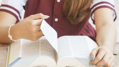 Ett lexikon ligger på ett bord. En person, där ansiktet inte syns, bläddrar i den tjocka boken.