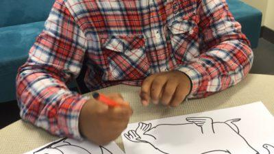 Malunde sitter och ritar vi ett bord. Han ritar en pingvin. Han har dreads och en rutig skjorta.