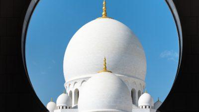 En stor vit moské med en blå himmel bakom.