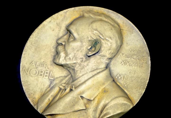Ett stort gyldmynt med en avbildning av Alfred Nobel.