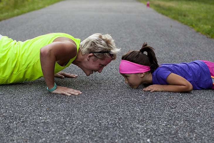 En vuxen person och ett barn ligger mitt emot varandra på marken. De gör push ups och har träningskläder.