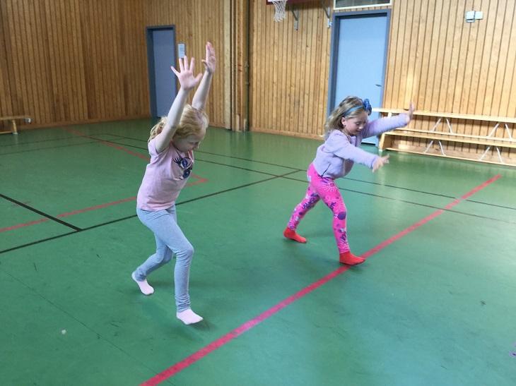 Saga och Melina står i en gymnastiksal. De har båda händerna i luften och är påväg att göra en kullerbytta.