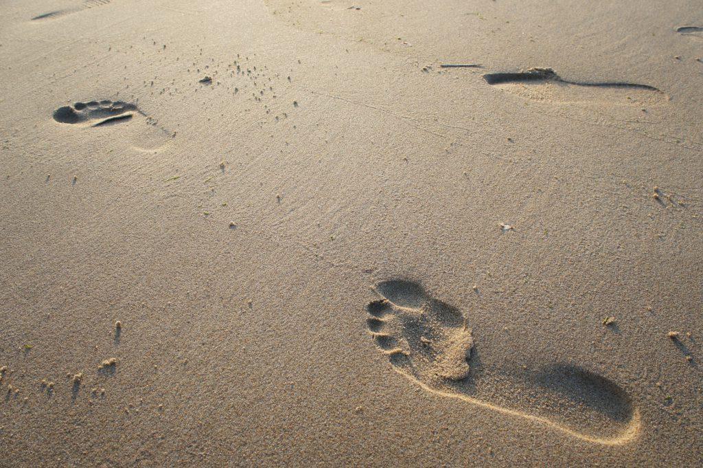 Två fotspår i sand.