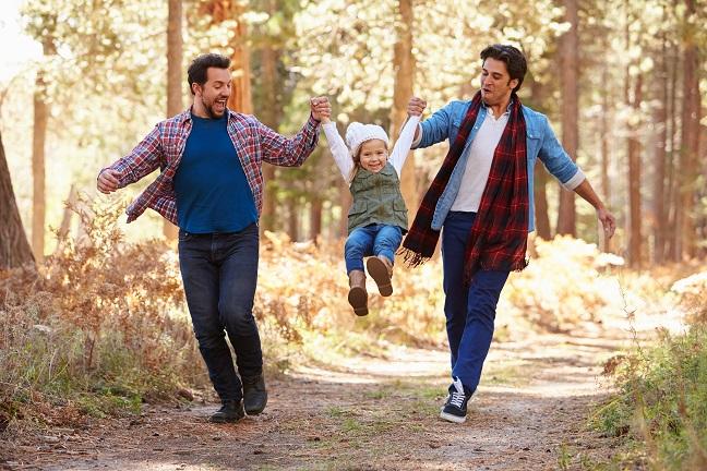 Två män håller en flicka i varsin hand och lyfter henne så hon kan hoppa högt.