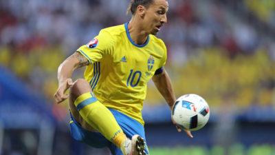 Zlatan plockar ner en fotboll från luften med ena foten. Han har gula och blå landslagskläder på sig och på tröjan syns siffran 10.