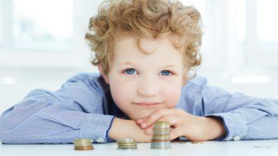 Ett barn med lockigt hår och blå ögon vilar sitt huvud på sina händer. Händerna ligger på ett bord och framför barnet på bordet ligger några högar med mynt.