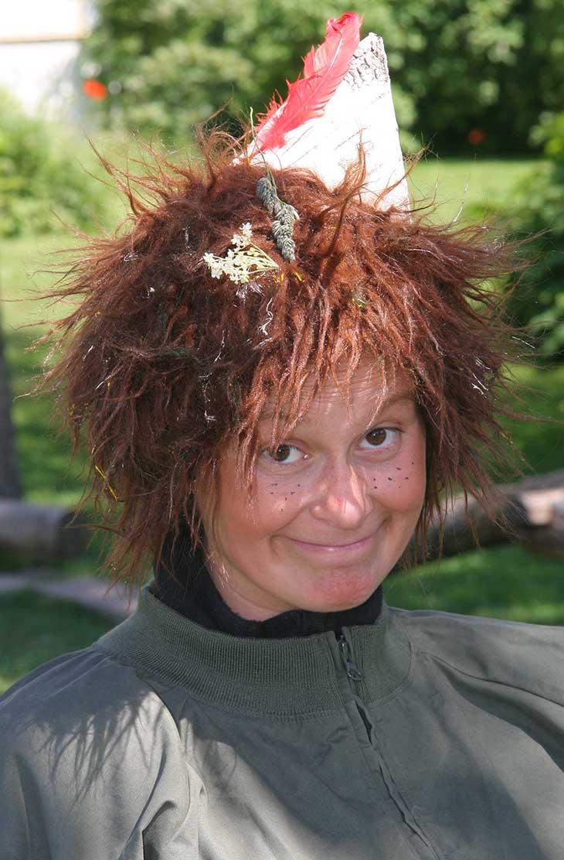 Närbild på Skogsmulle. SKogsmulle har gröna kläder, brunt rufsigt hår och en spetsig hatt gjord av vit näver.