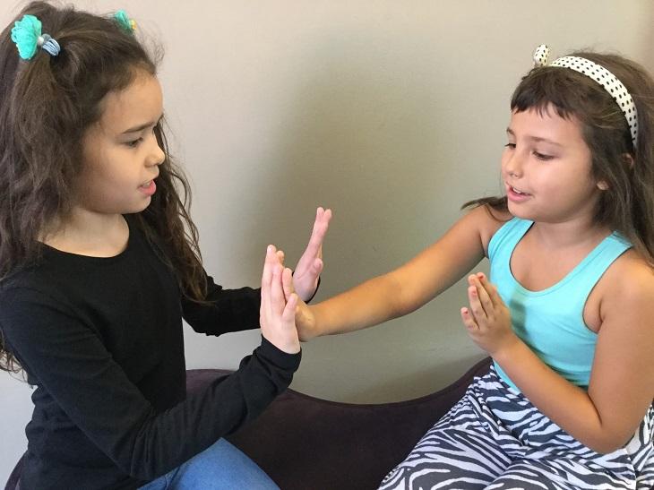 Sofie och Nour sitter på en bänk och klappar varandras händer. Båda har långt brunt hår, men den ena är lockig och den andra har hårband.