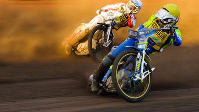 Två speedwaymotorcyklar åker på en grusbana. Båda förarna lutar cyklarna väldigt mycket och det sprutar sand. Båda har mycket skydd och stora hjälmar på sig.