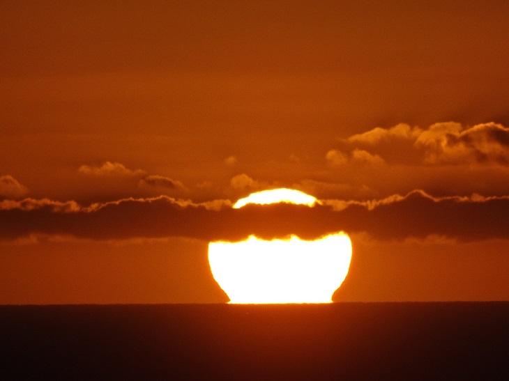 Solens syns vid horisonten med lite moln framför.