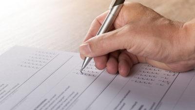 Ett papper med kryssrutor ligger på ett bord. En hand håller i en penna och kryssar i rutorna