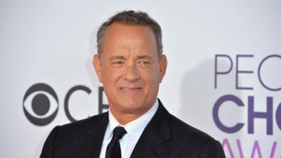 Tom Hanks står fram en vit vägg. Han har kort hår som är lite grått på sidorna. Han har kostym och slips på sig.
