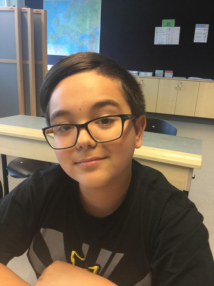Denis tittar snett upp mot kameran. han har kort svart hår som är struket åt sidan och fyrkantiga svarta glasögon.
