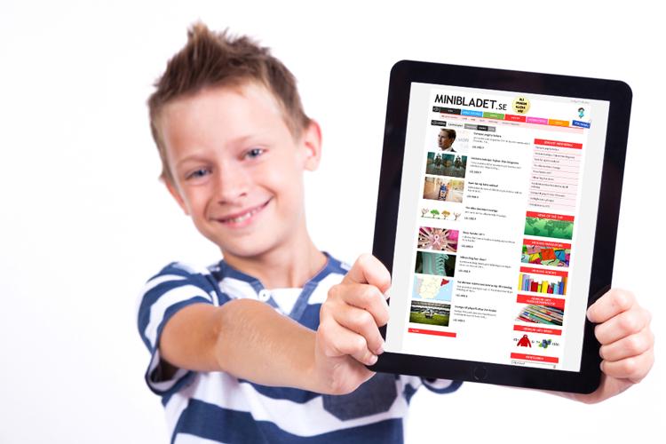 En pojke i blåvitrandig tröja som håller fram en surfplatta som visar MiniBladets webbsida