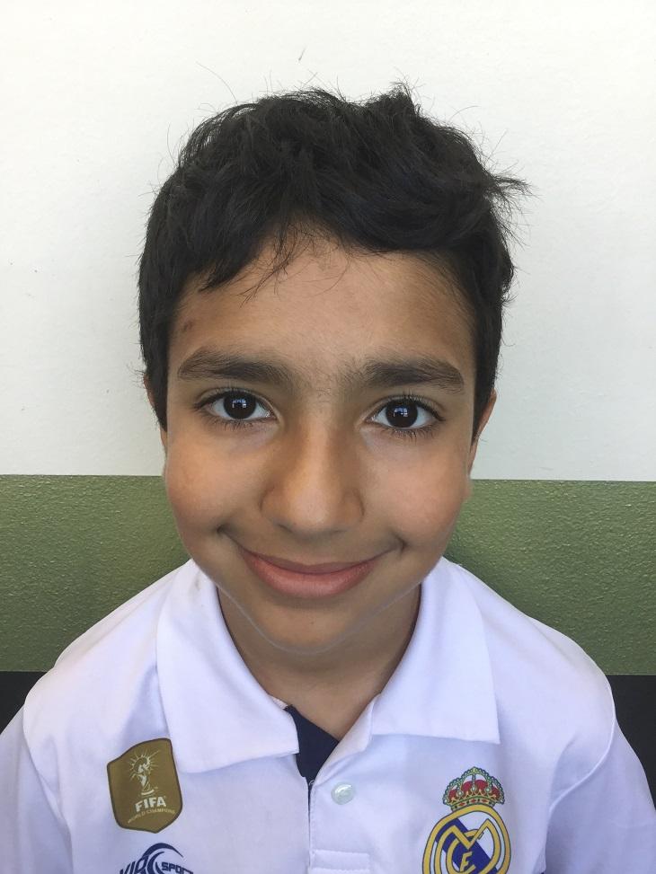 Hassan ler och tittar in i kameran. Han har kort svart hår och en vit tröja med krage.