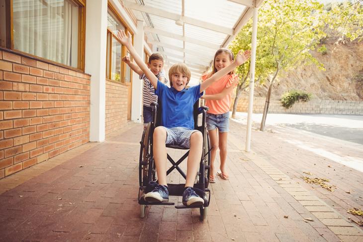 En pojke i blå tröja sitter i en rullstol. Han sträcker ut armarna och ser glad ut. Bakom honom står två andra personer och puttar på.