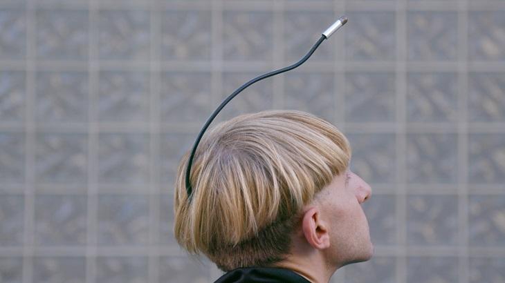 Ett huvud bakifrån på en kille. Han har blont tjockt hår. Ur hans bakhuvud sticker det ut en svart pinne som sträcker sig fram över hans huvud och slutar strax framför hans panna.