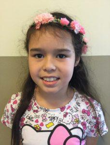Sofie har en hello kitty-tröja och ett diadem med blommar i sitt långa svarta hår.
