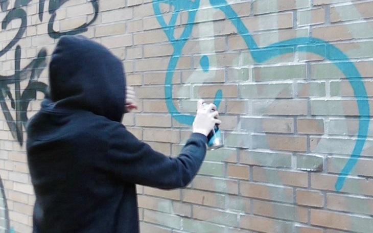 En person med mörk tröja och luvan uppdragen står vänd mot en vägg. Vi ser inte ansiktet. Personen har en sprejburk i handen och sprejar på en tegelvägg.