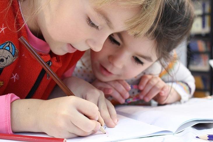 Två barn sitter lutade över en skrivbok där en av dem skriver noggrant.