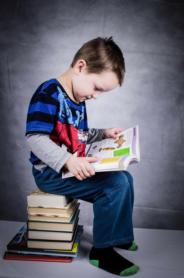 En pojke som sitter på en hög med böcker och läser.