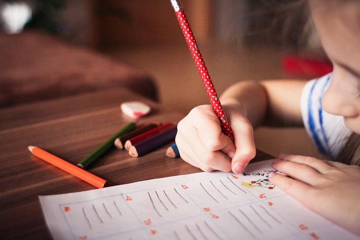 En flicka skriver med en röd penna på ett papper.