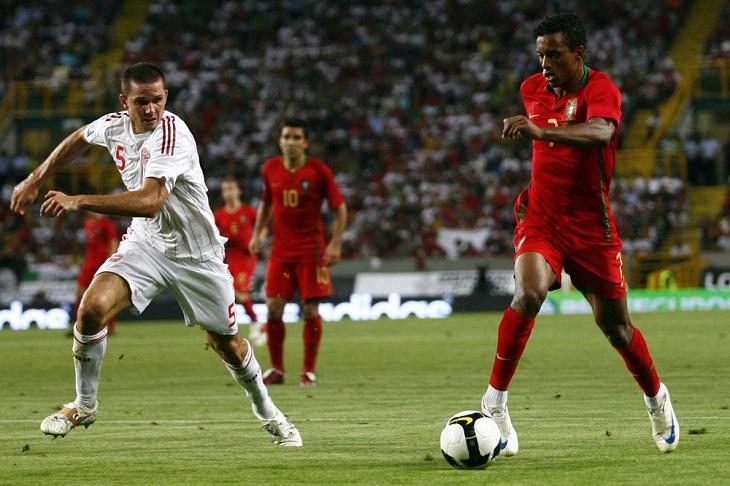 En fotbollsspelar i rött springer med bollen. Bredvid honom springer en spelar i vitt och försöker jaga ikapp honom. Bakom dem syns en stor fotbollsplan och en stor läktare.
