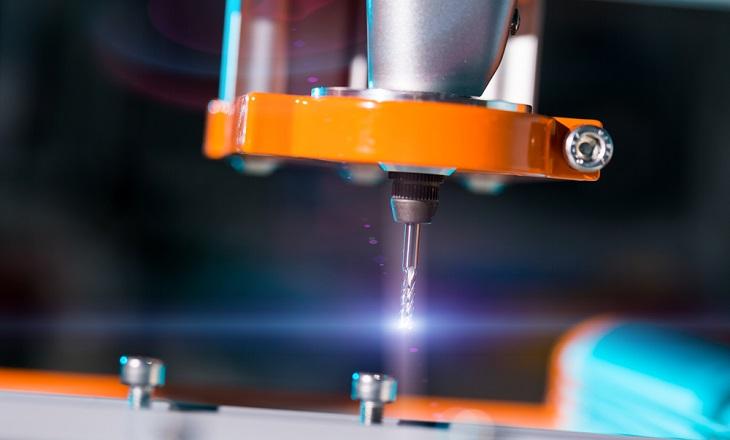 En stor metallarm närmar sig en skruv. Längst ut på metallarmen sitter en liten borr som glänser i ljuset.