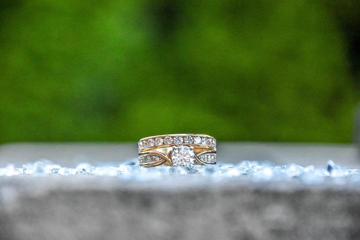 En ring ligger på en sten. Ringen är av guld och har en stor diamant i mitten och många små runt hela ringen.
