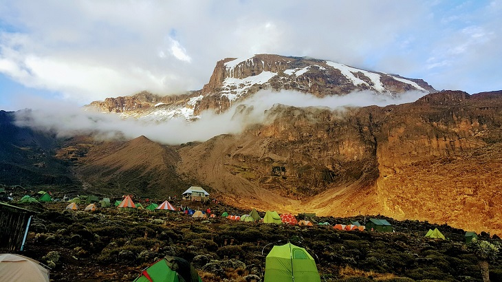 Ett stort brunt berg. Runt toppen på bergen ligger vita tunna moln och högst upp på berget ligget det snö.