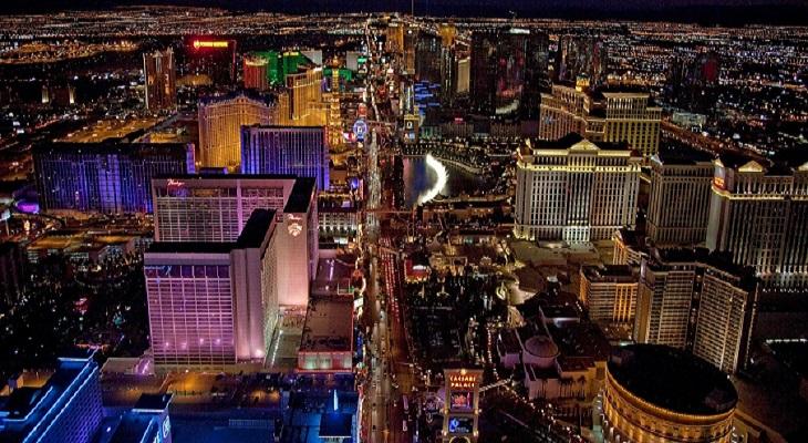 En vy ovanifrån av en stor stad. Det finns många skyskrapor och det lyser mycket olika neonljus.