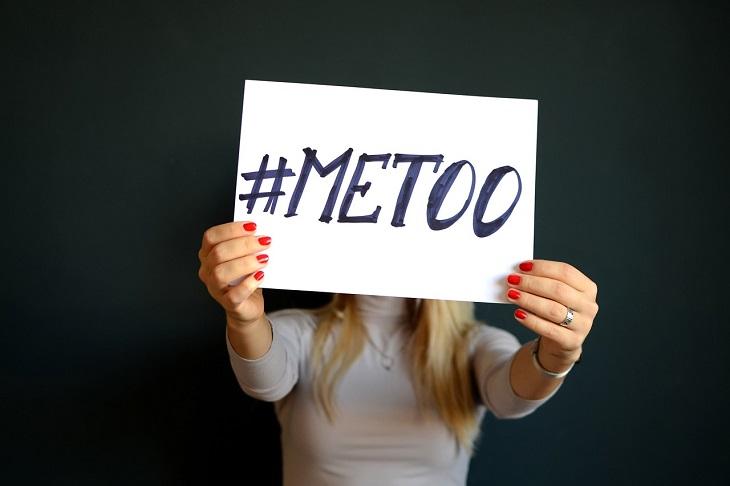 En tjej står mot en svart vägg. Vi ser inte hennes ansikte för framför sig sträcker hon fram en skylt där det står #metoo.