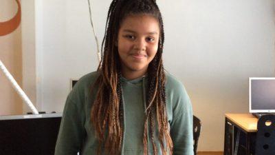 Miriam står och lutar sig mot en skolbänk. Hon har en grön hoodie och långa rastaflätor. Hon ler mot kameran.
