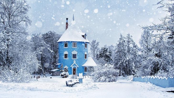 Muminhuset. Det är blått, runt och högt, som en cylinder. Det har en veranda och ett spetsigt tak. Huset och omgivningar är täckta av snö.