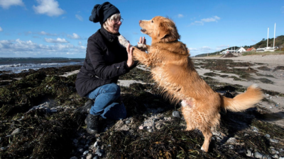 Hunden Nimbus står med tassarna mot sin matte Mariannes händer. Nimbus är ljusbrun med medellång päls. Marianne har blåa jeans och en svart sjal knuten runt huvudet. De står på en strand full med alger.