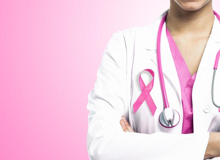 En läkare syns till hälften. Hen har vit läkarrock på sig och ett rosa stetoskop. På rocken sitter ett rosa band. Bakgrunden är rosa.