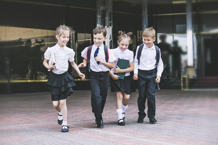 Fyra barn springer fram mot kameran. De har vita skjortor, svarta byxor eller kjolar och svarta blanka skor.