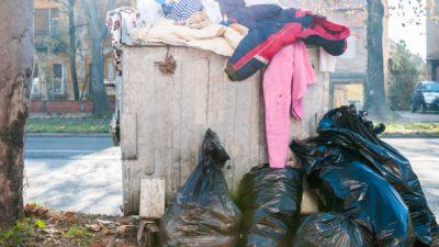 En stor container med sopor. Ur containern hänger det slängda kläder.