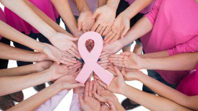 Massa händer sträcker sig in mot bildens mitt där det ligger ett rosa band.